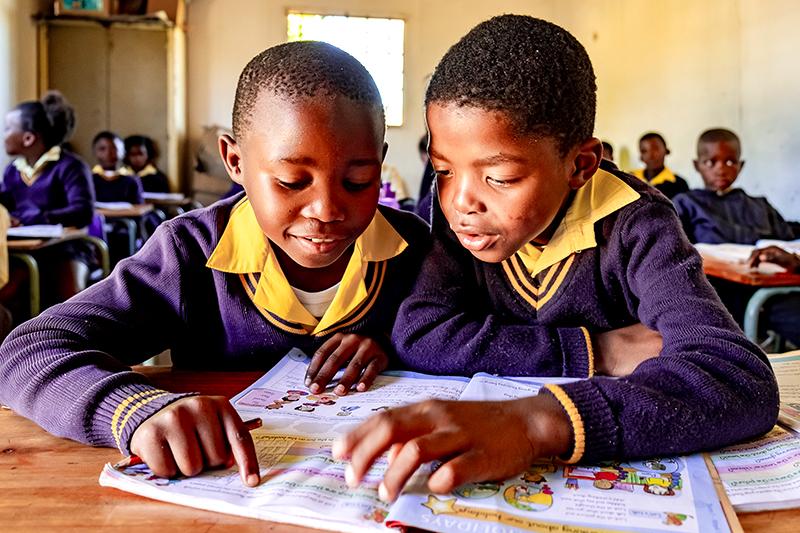 Twee kinderen zitten voorovergebogen en bekijken het lesboek in een Zuid-Afrikaanse klas