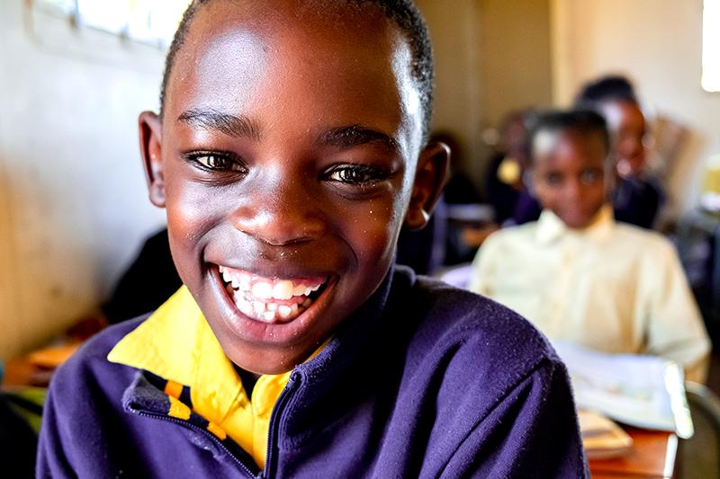 Een Zuid-Afrikaanse jongen heeft plezier in de les